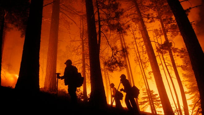 Firefighters watch a prescribed burn at the fire line while fighting the Angora Fire in South Lake Tahoe, Calif., Sunday, June 24, 2007.