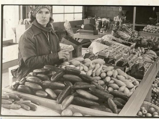 Christine Coates, aunt of Michael Coates, arranges a squash display in her WNC Farmers Market booth in 1981.