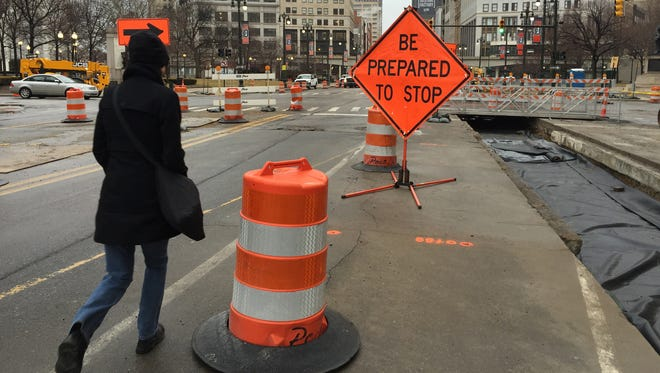 Pedestrians maneuver around orange construction barrels on Woodward Ave during the M1 construction project on Tuesday, March 31, 2015.