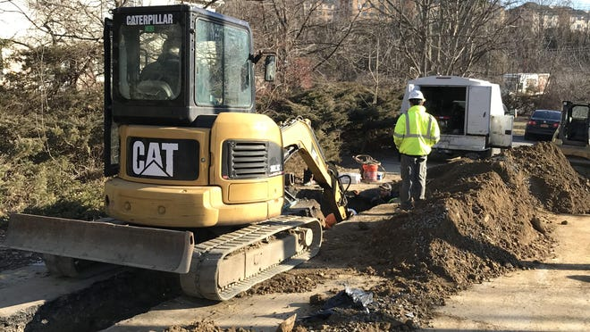 A contractor hired by the Village of Kiryas Joel installs a water main on Old Country Road in Monroe to supply homes in a small neighborhood where some wells have been depleted or weakened by Kiryas Joel's nearby municipal wells.