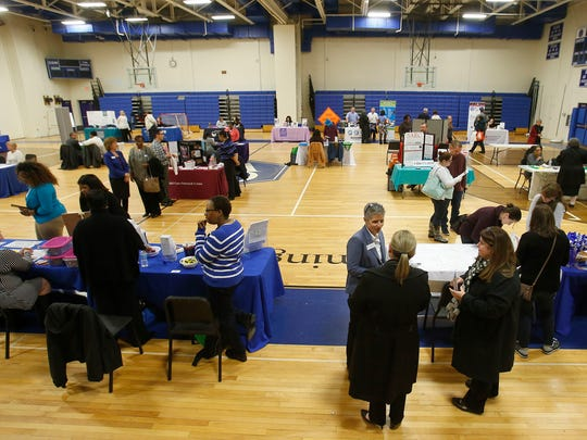 """Information booths fill the gymnasium before an Imagine Delaware forum """"Protecting Our Children"""" at Cab Calloway School of the Arts Friday."""