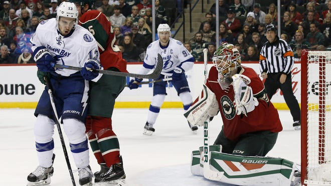 Minnesota Wild goalie Devan Dubnyk, front right, catches a shot in front of Tampa Bay Lightning center Cedric Paquette (13) and Wild defenseman Jonas Brodin, center, of Sweden, during the second period of an NHL hockey game in St. Paul on Saturday.