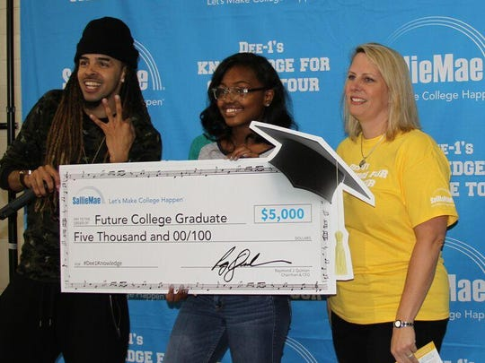 Destiny Broomer, a junior nurse technology student at St. George's Technical High School, receives a $5,000 college scholarship from Rapper Dee-1, left, and Sallie Mae rep Jennifer Chellew.