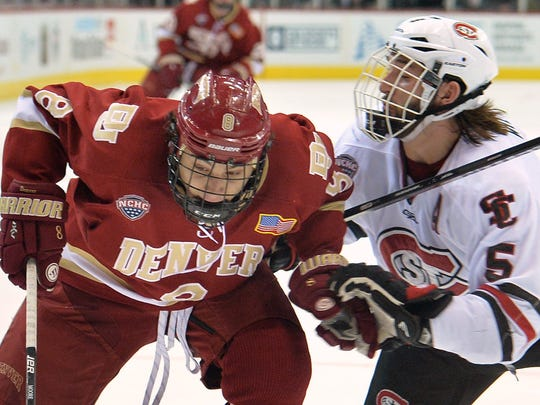St. Cloud State's Nathan Widman (5) pushes into Denver's Trevor Moore (8) during the first period of the NCHC Frozen Faceoff game Friday at Target Center in Minneapolis.
