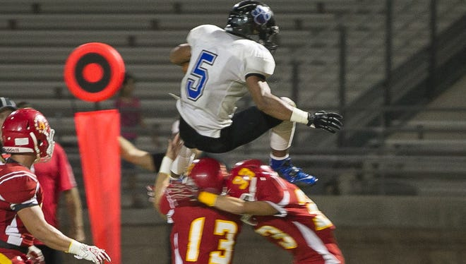 Orlando Wallace of Cathedral City leaps above Palm Desert defenders Friday during the Lions loss to the Aztecs. He injured his elbow on the play. Orlando Wallace (No. 5)  of Cathedral City leaps above Palm Desert defenders during a DVL football game held at Palm Desert High School Oct. 17, 2014.
