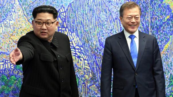 North Korea's leader Kim Jong Un (left) gestures next