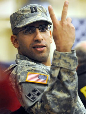 In this photo taken on Feb. 14, 2013, Capt. Florent Groberg watches the Change of Command ceremony for the 4th Infantry Brigade Combat Team at the Fort Carson Special Events Center, in Colo.