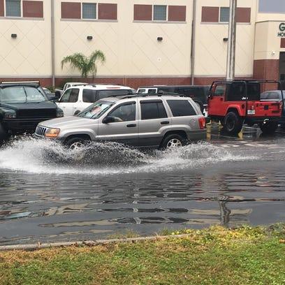 Cars at Melbourne High School slosh through puddles
