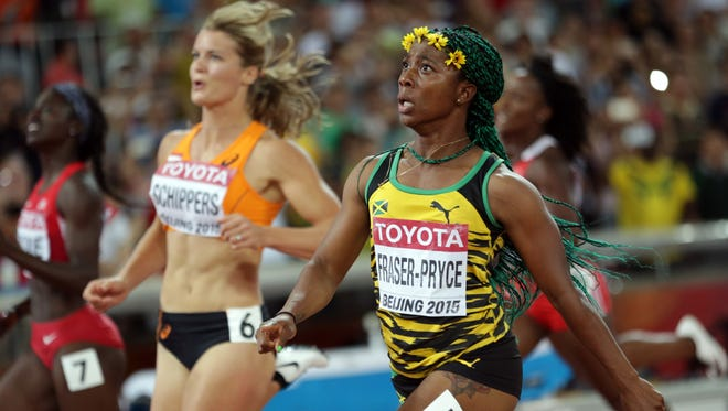 Jamaica's Shelly-Ann Fraser-Pryce, right, celebrates as she wins the gold medal in the women's 100m ahead of Dafne Schippers of the Netherlands at the World Athletics Championships at the Bird's Nest stadium in Beijing, Monday, Aug. 24, 2015.