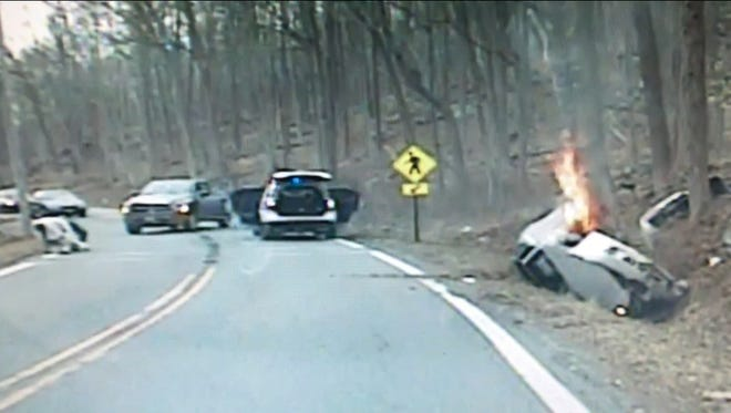 Screenshot from dashcam video showing Kinnelon Police rescuing a woman from her car, just before it burst into flames.