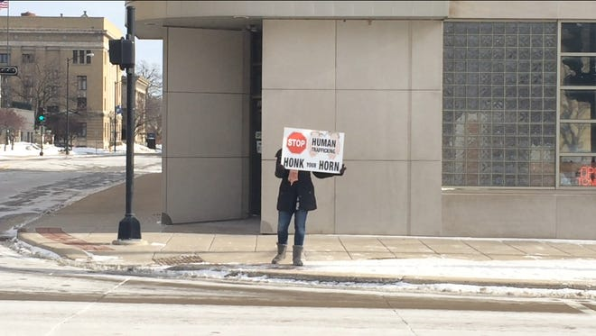 A volunteer fro Damascus Road encourages motorists to honk their horns to raise awareness about human trafficking on Monday, Jan. 11, 2016.