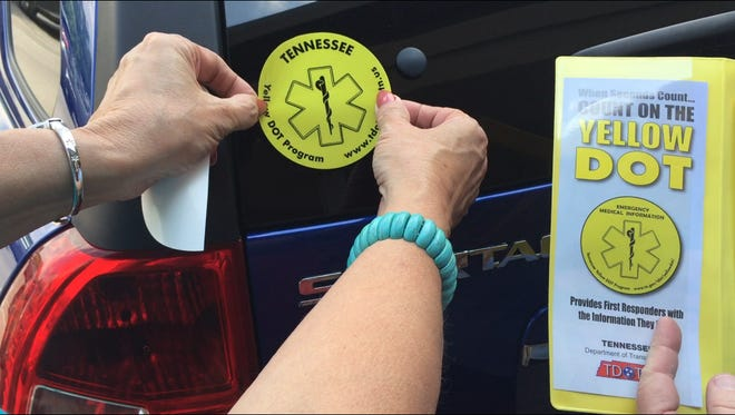 Madeline Methvin adheres a Yellow DOT sticker to her car so first responders know they can find her medical information inside the packet, shown at right, inside the glove box of her car.