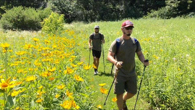 Michael Maziarka of La Crosse and Miles Vining of Bloomington, Indiana, walk through an prairie field on a segment of the Ice Age Trail located west of Madison.