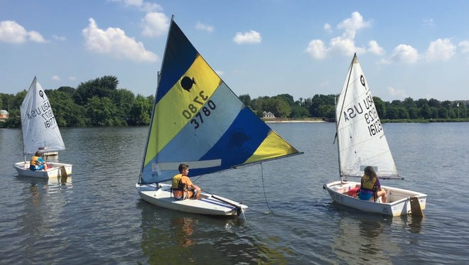 Joseph Linartas (center), 12, and other children learn to sail this month on the Cooper River in an on-the-water course offered by the Cooper River Yacht Club in Collingswood.