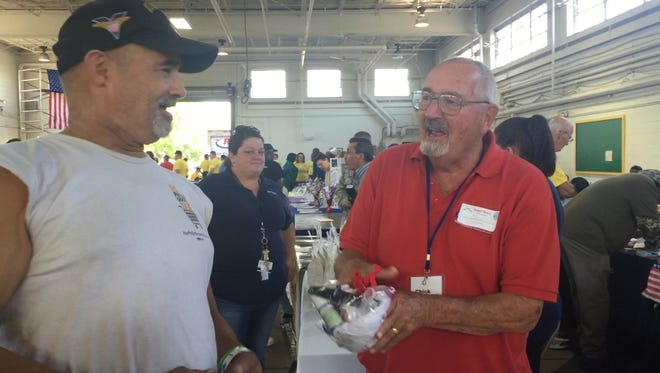 Red Cross volunteer Chick Warrington of Clementon  hands homeless Philadelphia vet Gui Leadum a bag of  toiletries at the Cherry Hill Armory  during the annual Stand Down South Jersey. No veteran is turned away.