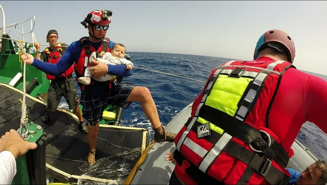 Estaban Guzman transfers a baby between boats off the coast of Libya in September 2016. Guzman and Jim Houck, both Poudre Fire Authority firefighters, were doing refugee rescue work for a disaster-focused non-profit.