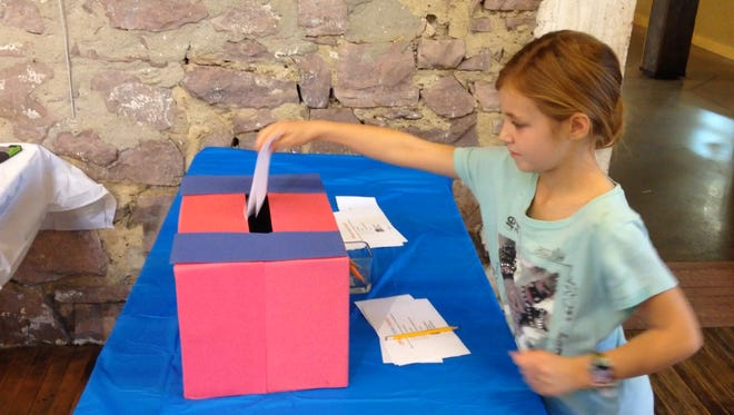 Josie Biteler, 7, votes for her favorite activity during an Election Day event hosted by the Museum of Visual Materials.