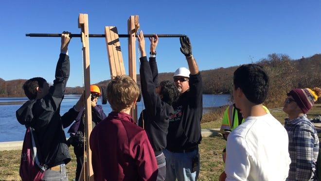 A Picatinny Arsenal engineer, in hard hat, inspects a trebuchet constructed by a team of students from Madison High School for a pumpkin-slinging contest at Picatinny Lake on Friday, Nov. 18, 2016.