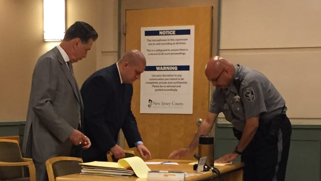 Suspended Millville Police Officer Jeffrey E. Proffit (center) is seen here with attorney Michael L. Testa Sr. at a Cumberland County Superior Court hearing.