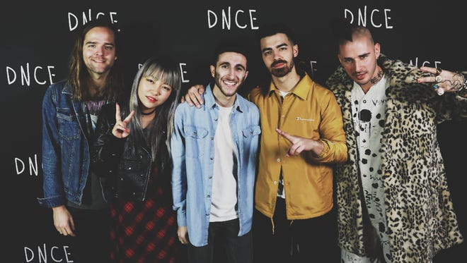 Joseph Karre, center, of ML1 Records in Lafayette stands with members of the rock band DNCE.