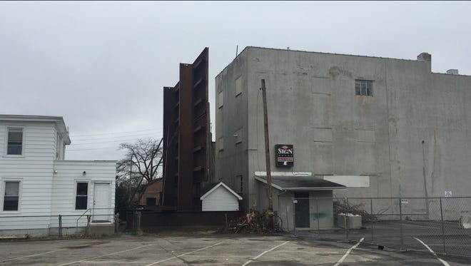 A three-story barrier was erected Saturday behind 109 E. Main St. in Millville. The city plans to demolish it. This view is from the eastern side of the building.