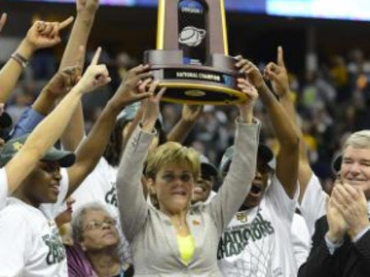 Baylor head coach Kim Mulkey raises the championship trophy with her team after beating Notre Dame to cap a perfect 40-0 season.