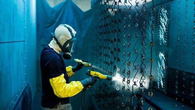 1. Michael Calloway powder coating steel washers at Residential Elevators' Cairo, GA manufacturing facility.