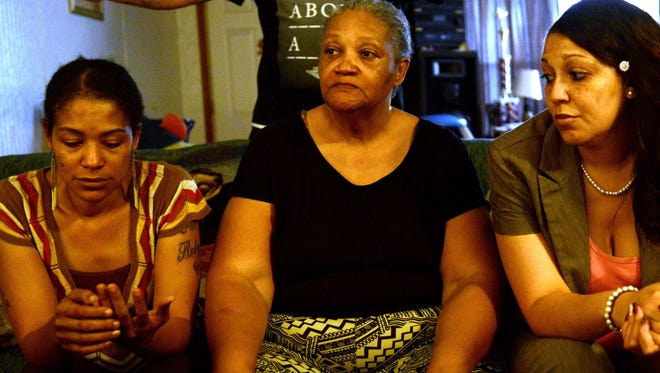 From left, Vallie Evita Bowman sits with her mother Alma Bowman and sister SoRay Bowman Woods and listen as Shaun Bowman (who asked not to have his face published) speaks about the murder of his father Walter Rodney Bowman at a family home Thursday evening.