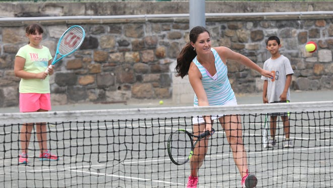 Ossining native Jamie Loeb plays tennis with children from the Ossining Day Camp tennis program at Nelson Park in Ossining Aug. 3, 2015