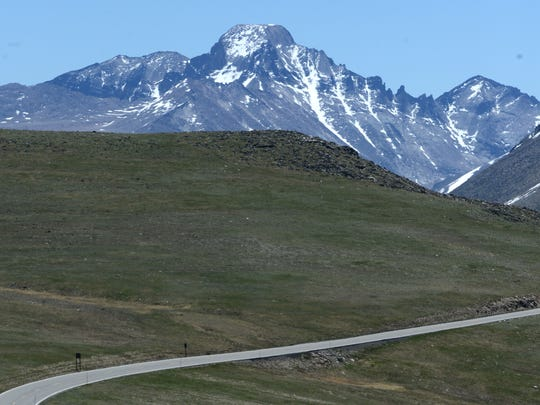 Longs Peak, left, and Mount Meeker, loom over Trail Ridge Road at Rocky Mountain National Park on June 20.