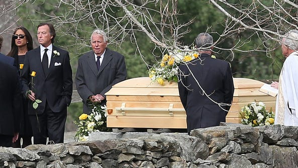 Eugene Colley stands near his wife's coffin at June