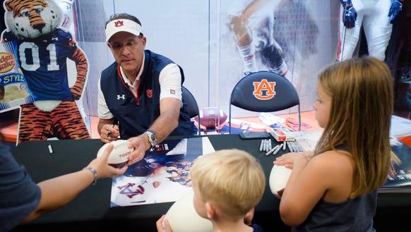 Auburn head coach Gus Malzahn signs footballs for fans