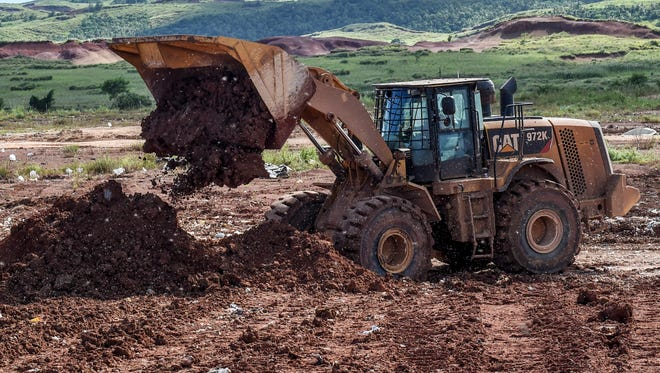 Swarms of flies cloud the air as a front-end loader covers a section of trash at the Layon Landfill in Inarajan on Oct. 2.