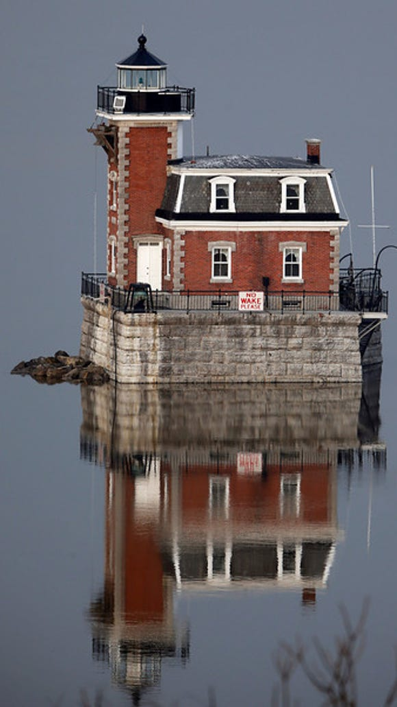 The Hudson-Athens Lighthouse is reflected in the Hudson River on Tuesday, Dec. 3, 2013, in Hudson, N.Y. (AP Photo/Mike Groll)