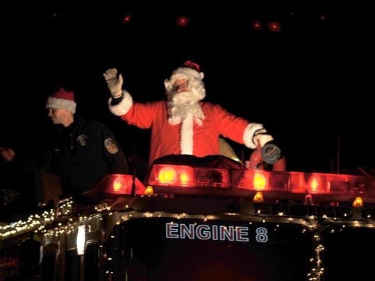 Santa Claus, portrayed by Randy Kepley, waves as he makes his way west on Route 422 aboard Cleona Engine 58-1 during his annual trip through Cleona Borough on Monday evening, December 21, 2015.