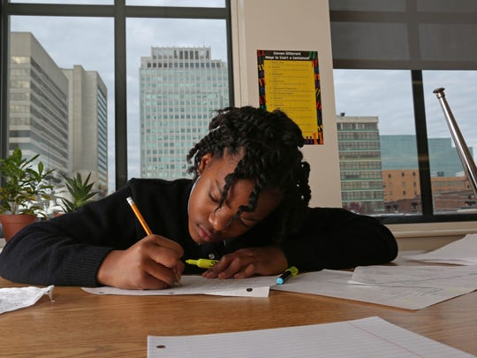 With the city of Wilmington skyline outside the window, Taliyah Duval, 11, a sixth-grader at Kuumba Academy in the Community Education Building, finishes writing a story about Greek mythology in this 2014 file photo.