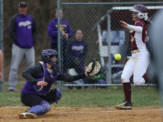 Arlington's Emery Gibbons begins to slide toward home plate during an April 2018 game against Clarkstown North.