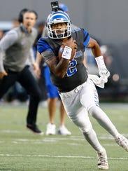 Memphis quarterback David Moore runs away from the