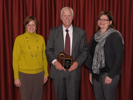 Tri-County Elementary School principal Shawn Jepson, left, and first-grade teacher Dianne George, right, accept the Wisconsin Title I School of Recognition award from Deputy State Superintendent Mike Thompson.