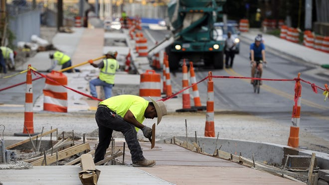 Jorge El Derado and other construction workers build part of a sidewalk along 11th Avenue in the Gulch as part of Mayor Karl Dean's $2.9 million complete streets project that was completed earlier this summer. With the approval of Amendment 3, projects like this could end up costing taxpayers more.