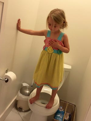 Stacey Feeley's daughter, 3, stands on a toilet in her Traverse City, Mich., home. She was practicing a lockdown drill for her preschool.