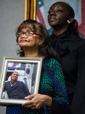Aieda Harris, mother of murder victim Edward Reeves, holds a photo of her son as she and Felecia Webster, mother of murder victim Kendrick Stokes, look on as the State Bureau of Investigation asks for help in the murder investigation during a news conference at the ALEA headquarters in Montgomery, Ala. on Friday May 25, 2018.