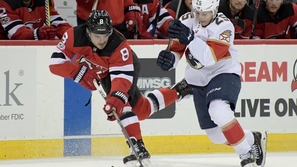 New Jersey Devils defenseman Will Butcher (8) skates with the puck as Florida Panthers left wing Henrik Haapala (25) defends during the first period of an NHL hockey game, Monday, Nov. 27, 2017, in Newark, N.J. (AP Photo/Bill Kostroun)