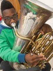 Tuba player Elijah Arthur of YPAS blows out a melody during the orchestra rehearsal.
