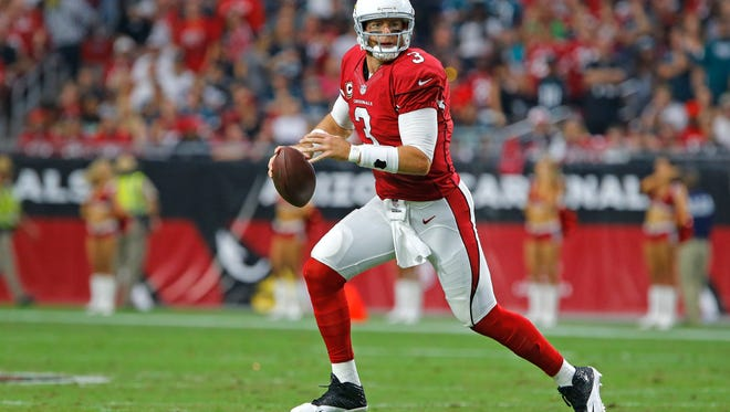 Arizona Cardinals quarterback Carson Palmer, here scrambling out of the pocket, has ties to Gilbert through his dad, Bill, who graduated from and played football at Gilbert High.