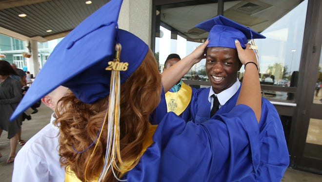 Husseini Husseini, right, receives some assistance with his graduation cap from Jade Moore just before their commencement ceremony for the Valley High School at the Kentucky Exposition Center.  