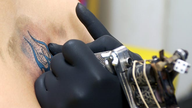 A Wichita Falls' tattoo artist places some permanent ink on a client. The Air Force is loosening its regulations on the amount of tattooing an airman can have.
