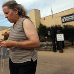 Mary Roy, of Potosi, Mo., holds a rosary in support of a pro-life rally Tuesday outside Planned Parenthood in St. Louis. Anti-abortion activists have released a second video.