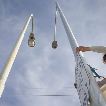 Javier Bueno transfers a sign to a new LED streetlight pole in Peoria. The old light (left) was to be removed as Peoria swapped out streetlights in a neighborhood near City Hall for the more energy-efficient LED lights as part of the city's effort to become more sustainable.
