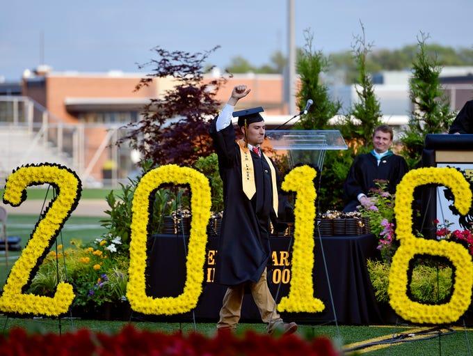 Senior Ian Adler raises his fist after giving a commencement